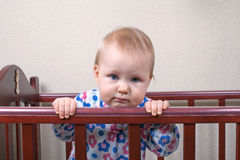 Sad baby girl standing in a crib Royalty Free Stock Photography