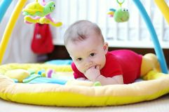 Sad baby on playmat Royalty Free Stock Photos