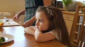 Sad baby is sitting at the table in the kitchen. The child does not want to eat, problems with appetite, a healthy