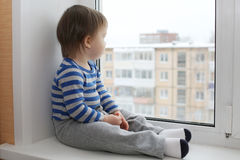 Sad baby sitting on window sill Stock Photos