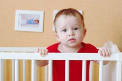 Sad baby standing in white bed Stock Image