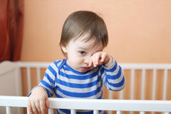 Sad baby in white bed Stock Photography