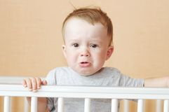 Sad baby in white bed. Sad baby age of 10 months in white bed Stock Photo
