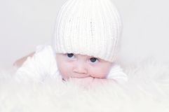 The sad baby in a white knitted hat Royalty Free Stock Photo