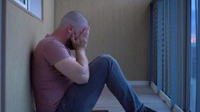 Sad Bald Brutal Man Sits on the Floor, Crying, Wiping Eyes, Alone. Apartment, Emotions and Drama Concept. Sadness