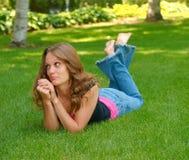 Sad, barefoot teen. A sad teen laying in grass Stock Photography