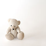 Sad bear-toy in stripes. On the white background Stock Images