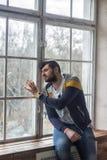 Sad bearded man looking through the window Royalty Free Stock Image