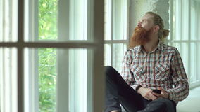 Sad bearded man sms texting using smartphone sit at windowsill at home stock video footage