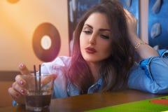 Sad beautiful adult girl drinking cocktail at bar Stock Photos