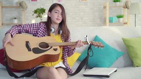 Sad beautiful Asian girl with long hair in the living room of a modern home having trouble learning to play acoustic. Portrait of a sad beautiful Asian girl with stock footage
