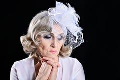Sad beautiful elderly woman on a black background Stock Photo