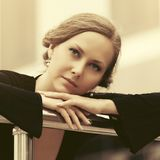 Sad beautiful fashion woman in black blouse leaning on railing royalty free stock photography