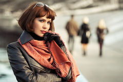 Sad beautiful fashion woman in leather coat walking in city street royalty free stock photography