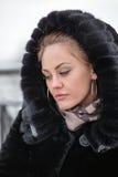 Sad beautiful girl in a fur coat. Stock Image