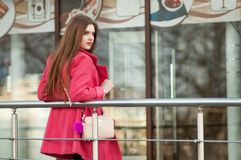 Woman in pink coat waiting bye at the window of the restaurant Royalty Free Stock Image