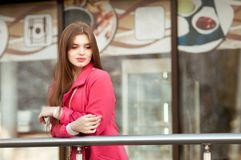 Woman in pink coat waiting bye at the window of the restaurant Stock Images