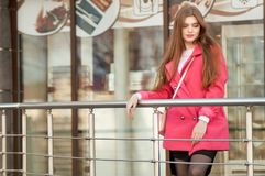 Woman in pink coat waiting bye at the window of the restaurant Stock Photography