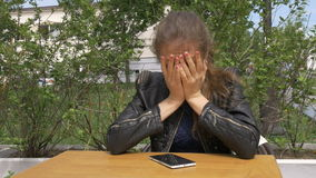 Sad beautiful girl sitting at a table in a cafe. Reads sms on a smartphone. Has hugs his head with his hands Sadness and