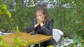 Sad beautiful girl sitting at a table in a cafe. Reads sms on a smartphone. Sadness and longing, hopelessness. stock footage
