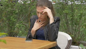 Sad beautiful girl sitting at a table in a cafe. Reads sms on a smartphone. Sadness and longing, hopelessness. stock video