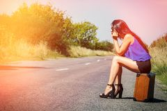 Sad beautiful girl traveler with suitcase on road, hitchhiking. Concept of travel, adventure, vacation, freedom. Waiting for car o Royalty Free Stock Images