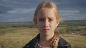 Sad Beautiful teen girl is looking with serious face at camera. stock video