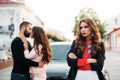 Sad beautiful woman with folded arms in fashionable clothes against kissing couple.