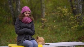 Sad beautiful woman freezing in autumn park, cold autumn. She is feeling cold and trying to keep warm. slow-motion. Beautiful woman freezing in autumn park, cold stock video footage