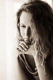 Sad beautiful woman with long curly hairs looking down Stock Photography