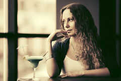 Sad beautiful woman with long curly hairs at restaurant Royalty Free Stock Images