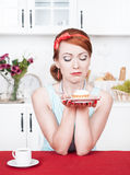 Sad beautiful woman looking on cake Royalty Free Stock Photos