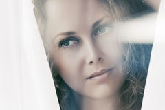 Sad beautiful woman looking out window Royalty Free Stock Photography