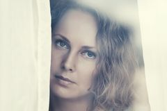 Sad beautiful woman looking out window Stock Images
