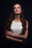 Sad beautiful woman looking up. On black background Royalty Free Stock Image