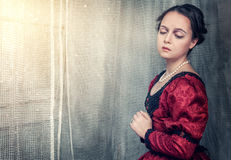 Sad beautiful woman in medieval dress near window Stock Photos