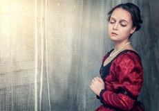 Sad beautiful woman in medieval dress near window Stock Photos
