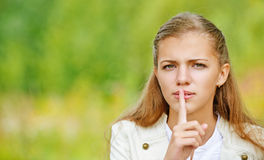 Sad beautiful woman puts finger to her lips Stock Image