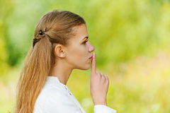 Sad beautiful woman puts finger to her lips Royalty Free Stock Photo