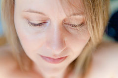 Sad Beauty. Eyelashes in focus, a beautiful woman with lovely features, bright eyes and smooth skin looking down. The image orientation is horizontal and there Stock Images