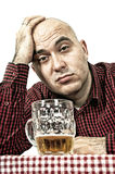 Sad beer drinker. Bald beer drinker sitting in the bar with a glass of cold lager on the table, sad face - depression concept Royalty Free Stock Photography