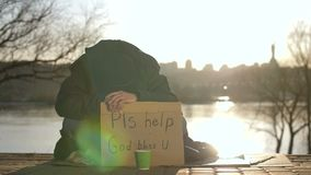 Sad beggar sitting with head down asking for help. Sad broken beggar sitting on the street with his head down, asking for help at sunset on the river bank in stock video