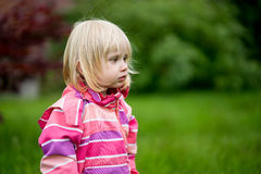 Sad or bewildered girl. Standing alone in the garden Royalty Free Stock Photos