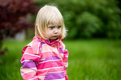 Sad or bewildered girl. Standing alone in the garden Stock Photo
