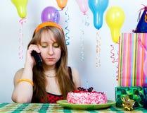 Sad birthday. Young sad girl talking on the phone Royalty Free Stock Image