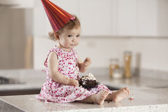 Sad birthday girl eating cake. Cute baby girl eating cake in the kitchen counter Royalty Free Stock Photo