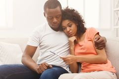 Sad black couple after pregnancy test result. Sad african-american couple after negative pregnancy test result, sitting on couch at home, copy space stock photos