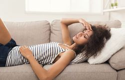 Sad black girl feeling pain lying on sofa. Sad girl with headache. Young african-american woman feeling pain, lying on sofa at home, copy space Stock Photos