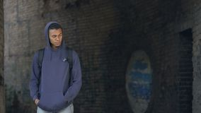 Sad black teenager walking alone abandoned building, puberty loneliness, problem