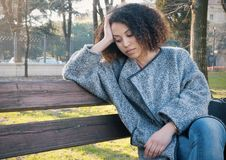 Sad black woman seated alone on a bench Stock Photo